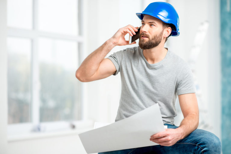 A construction business owner talks on cell phone about reducing overhead and driving profit.