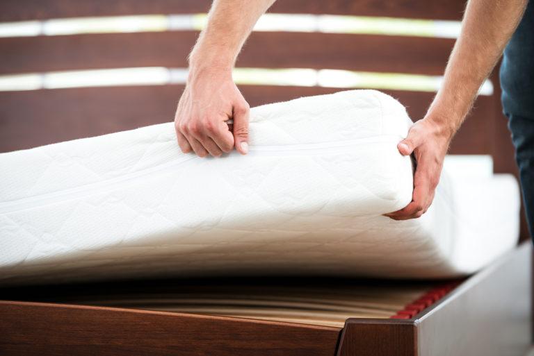 A man lifts a mattress off of a bed frame.