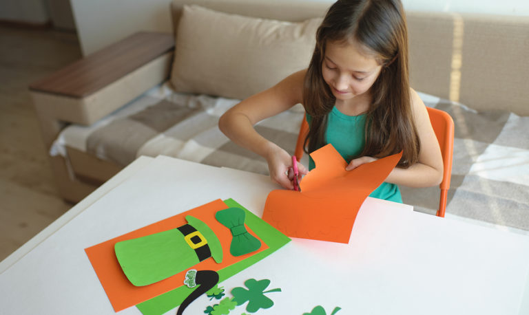 A young girl cuts out a Saint Patrick's Day craft.