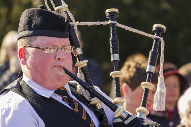 A man plays the bagpipes.