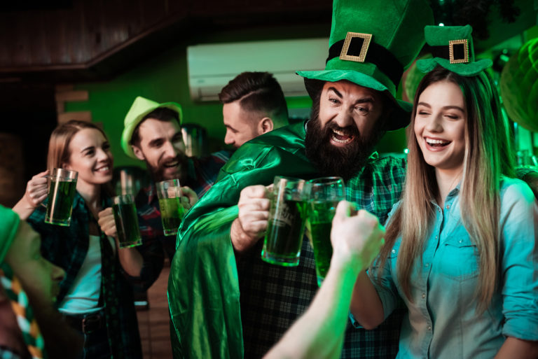 A group of people celebrate Saint Patrick's Day at a bar.