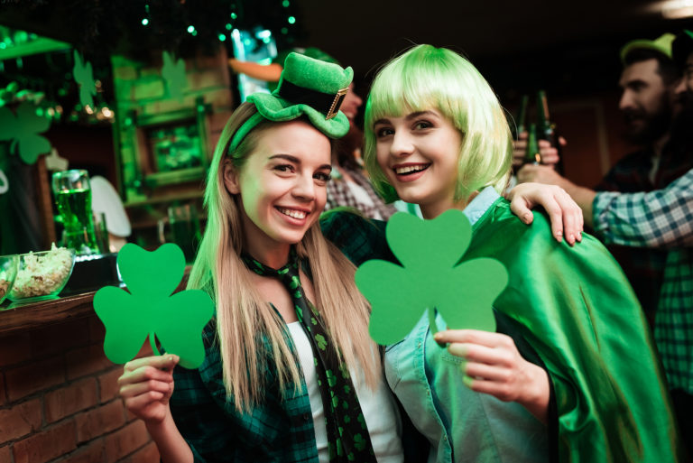 Two women wearing green in a pub pose for the camera on Saint Patrick's Day.