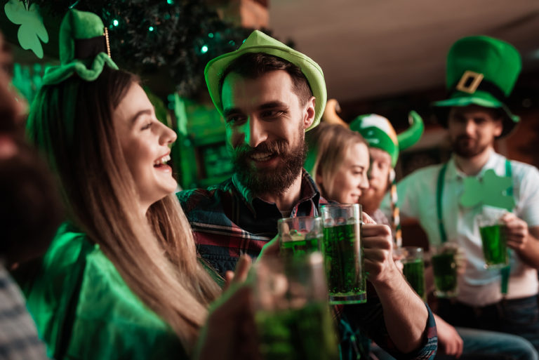 A group of green-clad revelers enjoys Saint Patrick's Day in a bar.