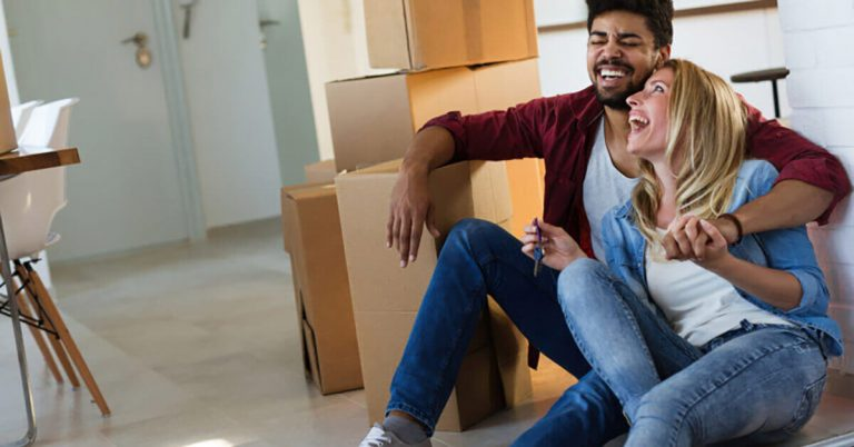 A young couple smiles and laughs while sitting by their moving boxes.