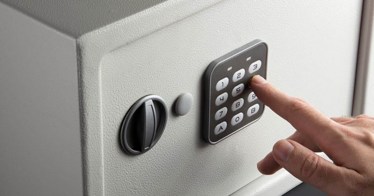 A close-up shot of a man's hand as he enters his code on his small home safe.