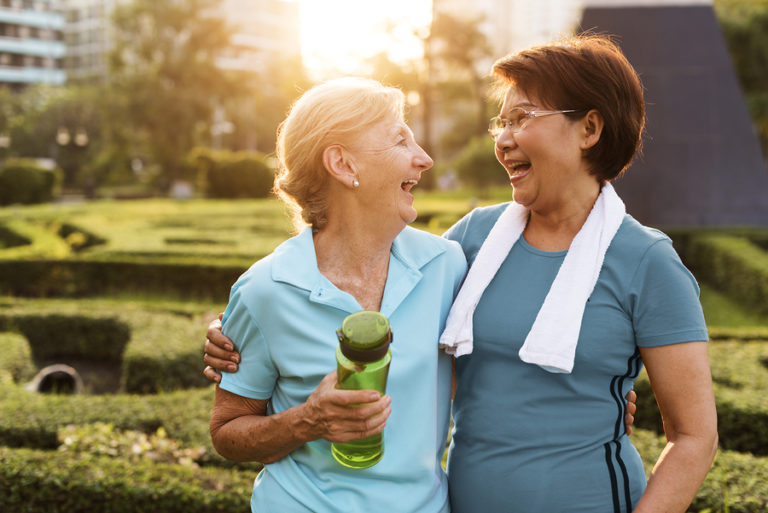 Two senior women share a quick hug and a laugh as they stand outside a senior living community wearing exercise clothing.
