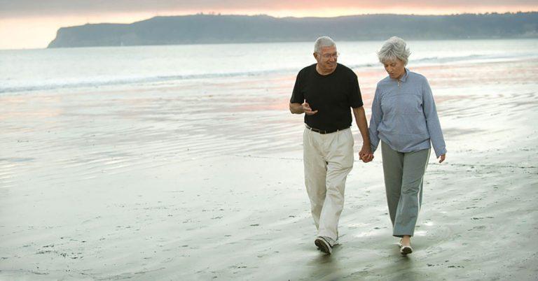 An elderly couple walk along a beach front.