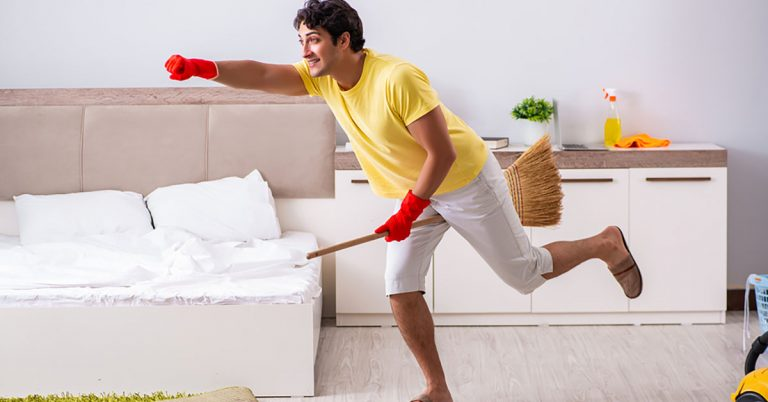 A young man pretends to ride a broom while cleaning his bedroom.