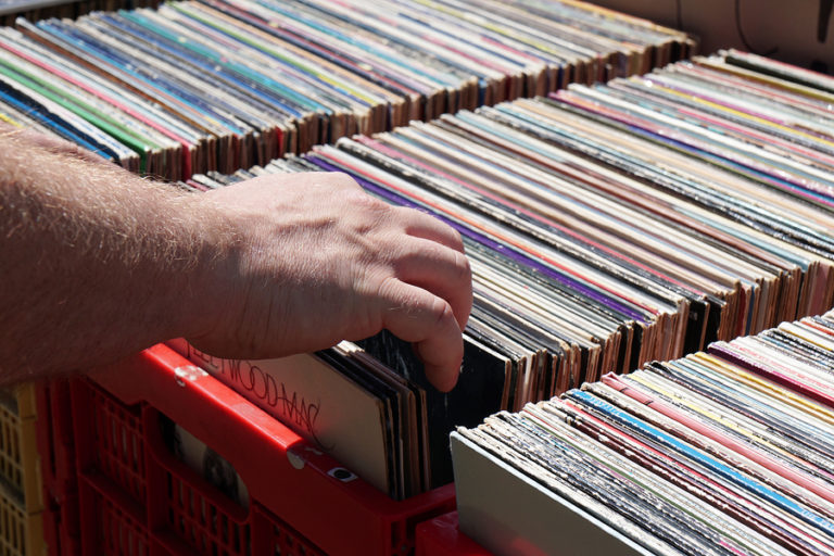 A close-up shot of a man's hand placing vinyl record albums in storage crates.