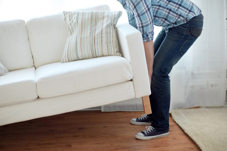 A young man lifts up one end of a couch to move it into storage.