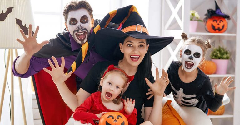 A young family poses in spooky Halloween costumes.