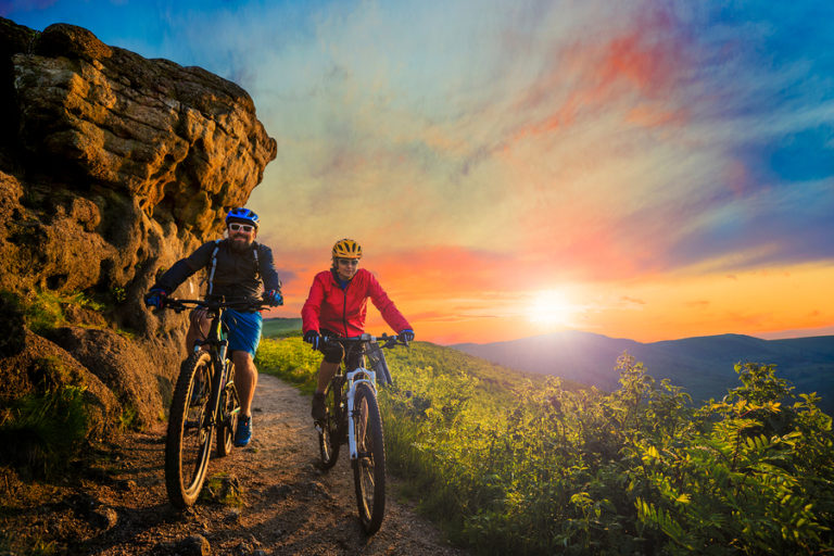 An older couple goes mountain biking as the sun sets behind them.