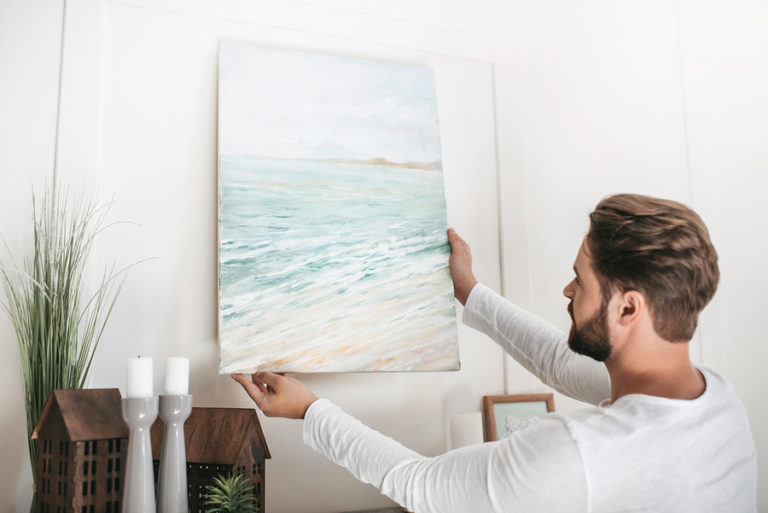 A young man holds a watercolor painting up against a wall