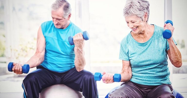 A couple works out on exercise balls with weights at a senior living community.