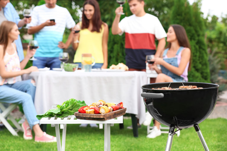 A group of people gather around a table and a grill at an outdoor party.