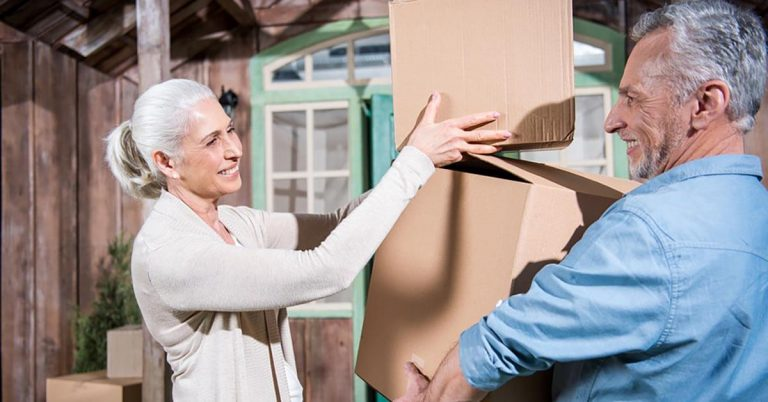 A senior couple carries boxes into their new home.