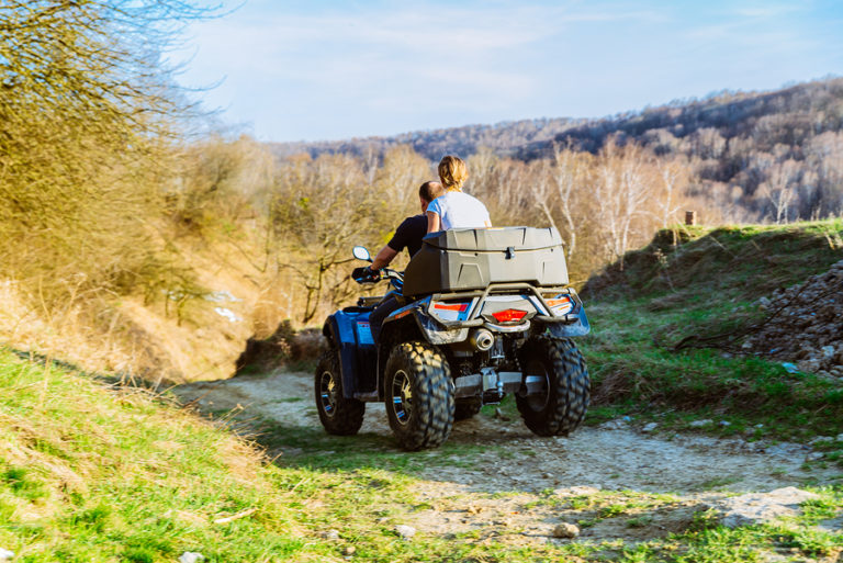 Two people on an ATV ride over a forest hill.
