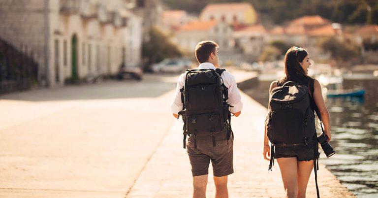 A young couple with backpacks walks among ruins.