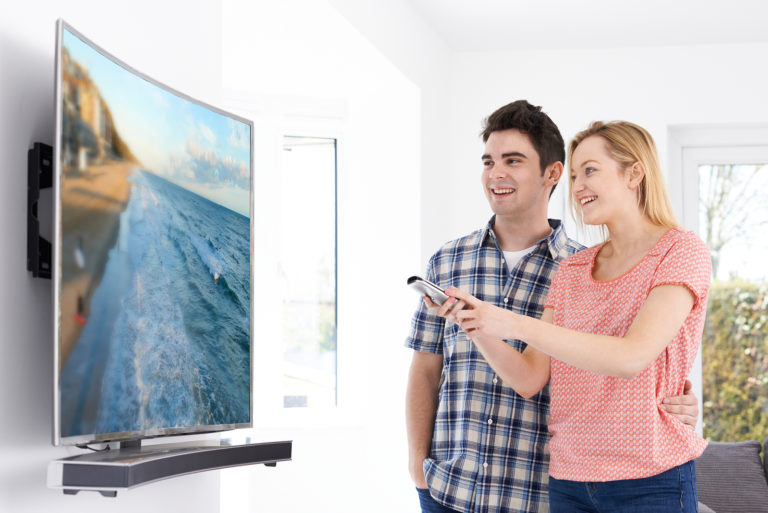 A couple stands in front of their new curved TV.