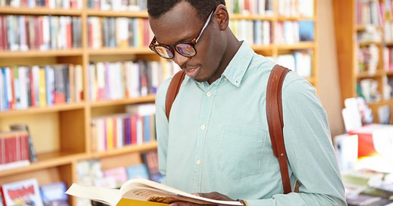A young man with a backpack and glasses checks out a book in a used bookstore.