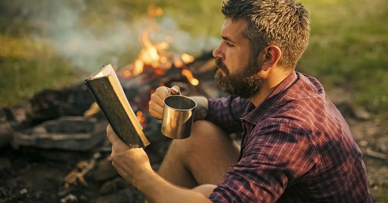 A man wearing a flannel shirt reads a book next to a campfire while drinking out of a tin mug.