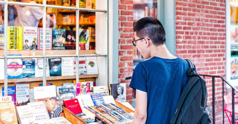 A young man checks out the books in a cart near the entrance to a used bookstore.