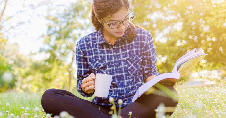 A young woman sits cross-legged in the grass immersed in a book