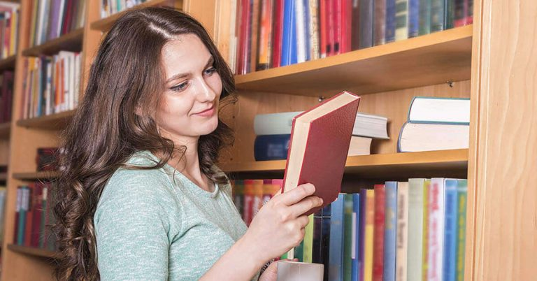 A young woman browses in a used bookstore