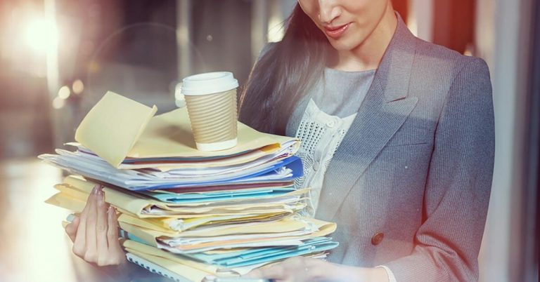 A businesswoman carries a stack of papers on which she is balancing a cup of coffee.