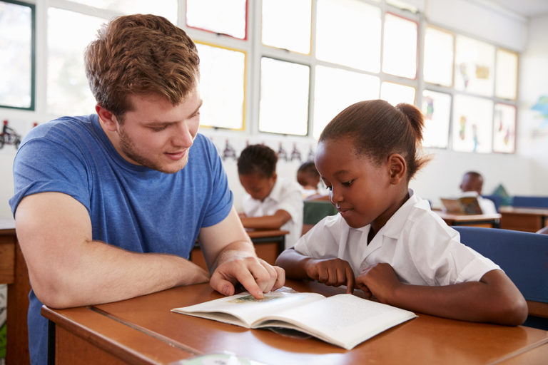 A teenage boy helps a young girl read.