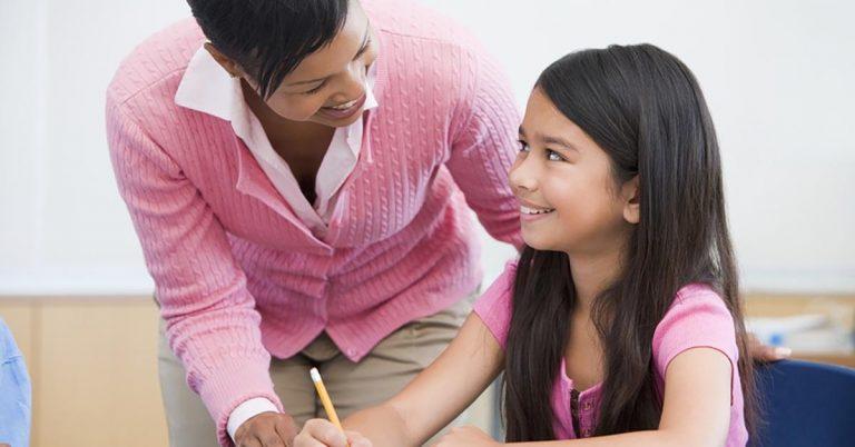 A teacher helps a girl.