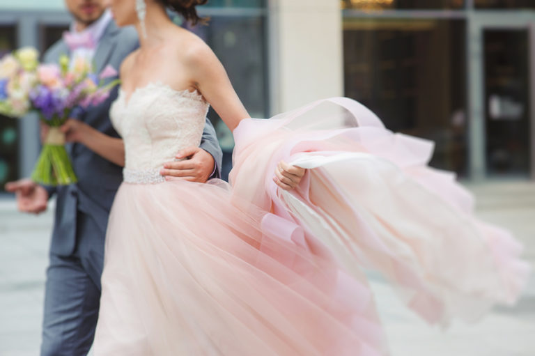 A groom has his arm around his bride's waist as they walk on a downtown street.