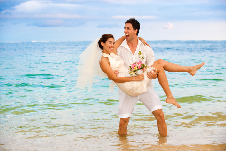 A groom holds his new bride in the surf on the beach. The sun shines and the couple laughs.