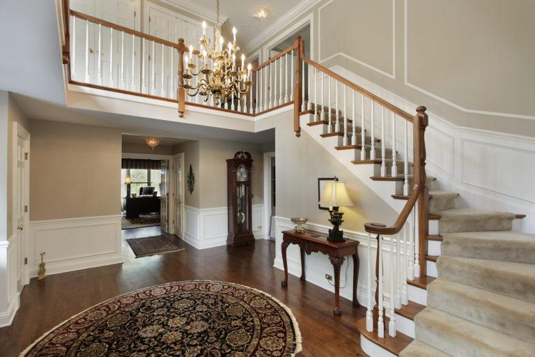 An elegant foyer with a brass chandelier