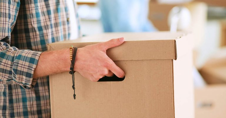 A close-up of a man's arms as he carries a large cardboard box.