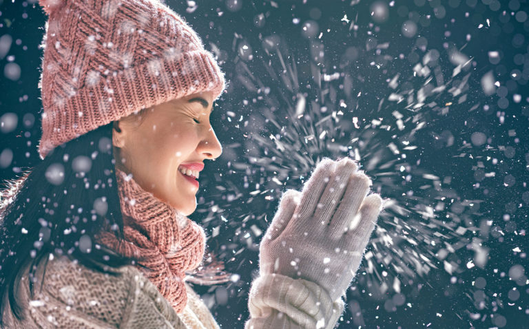 A woman who is bundled up for the cold claps her hands as it snows outside.