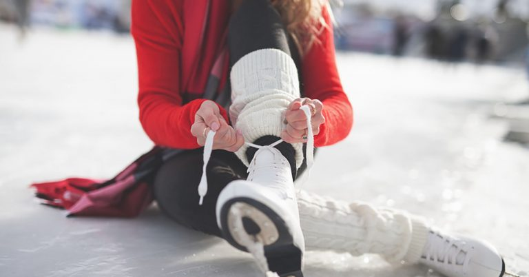 A woman ties her ice skates.
