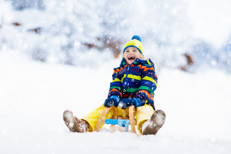 A young child sledding in the snow.