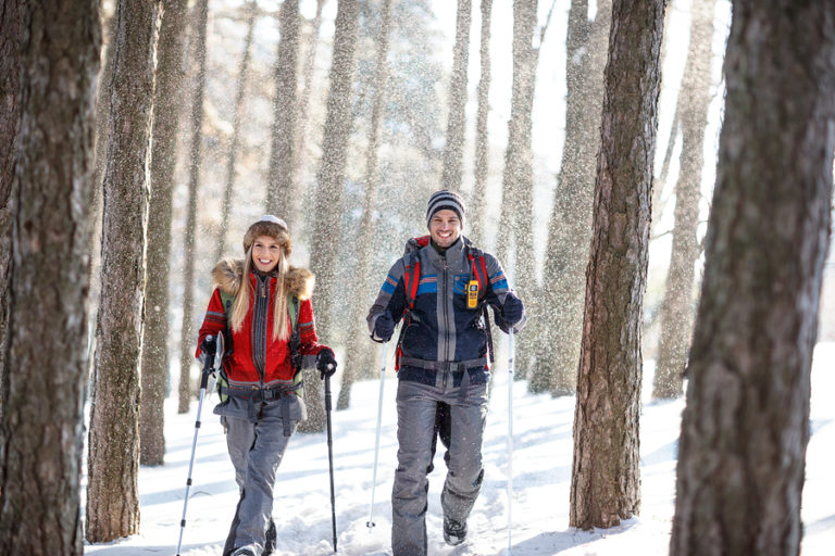 A young couple snowshoe in the forest.