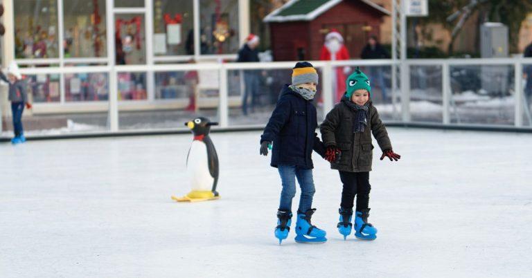 Two children inside of ice skating rink.