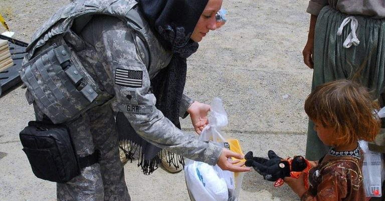 Soldier gives toy to a child.