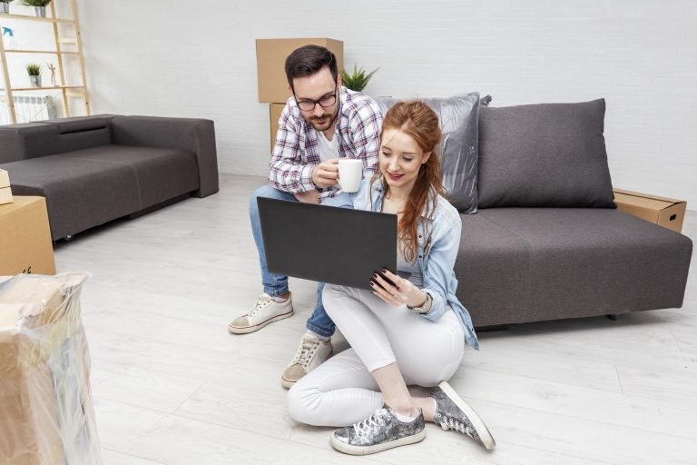 a couple sitting on on the floor and on the couch surrounded by boxes are both looking at a computer screen while they weigh their storage options